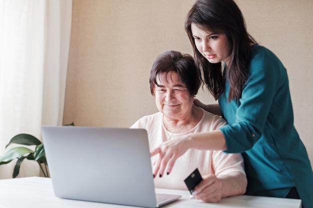 Молодая женщина помогает пожилой женщине делать покупки в интернете