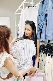 쇼핑몰에서 작업을 위해 블라우스를 선택하는 친구를 돕는 젊은 여자