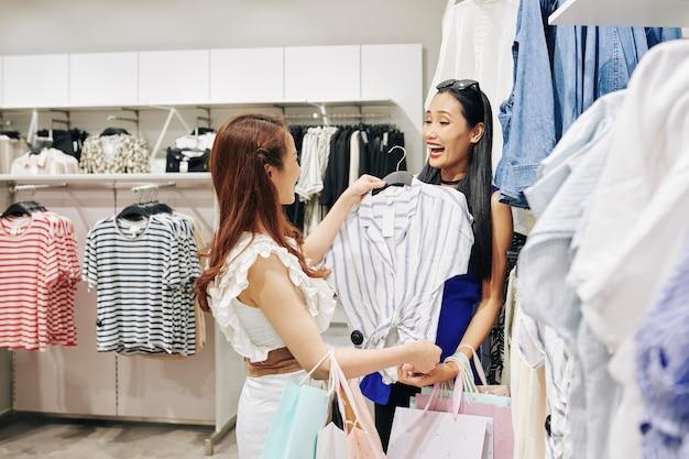 쇼핑몰에서 작업을 위해 블라우스를 선택하는 웃음 친구를 돕는 젊은 여자