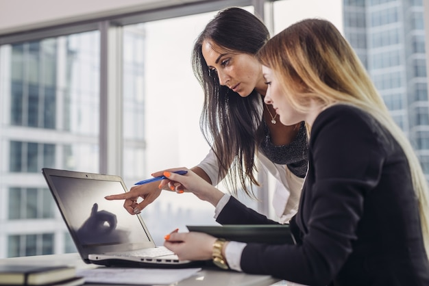 ノートパソコンの画面を指して情報を説明する学生を助ける若い女性