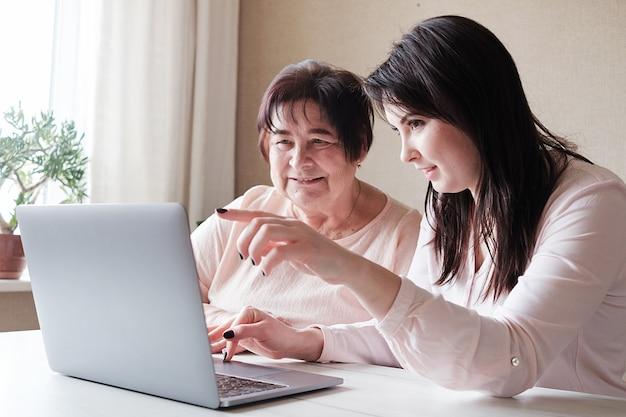 Молодая женщина помогает пожилой женщине пользоваться компьютером