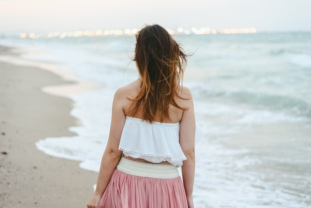 Young woman on her back on the beach walking lonely and sad.