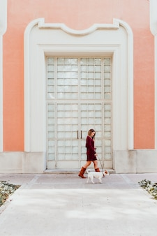 Young woman and her cute jack russell dog walking by the city
