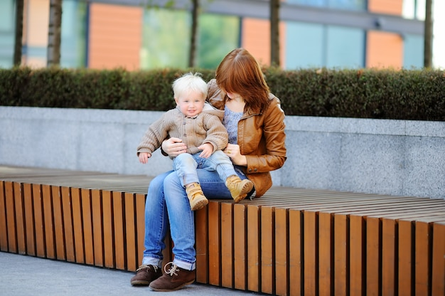 Young woman and her cute toddler son playing outdoors at sunny spring or autumn day