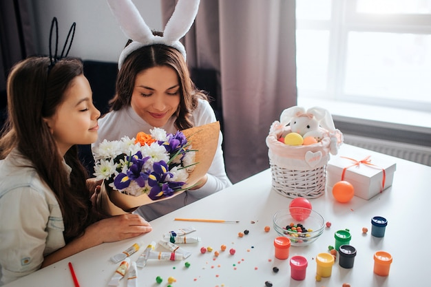 Young woman and her daughter prepare for easter. they smell flowers together. paint with sweets and decoration on table. daylight.