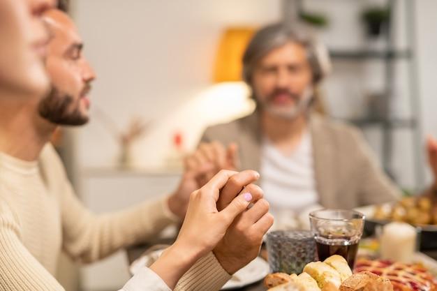 Молодая женщина, ее муж и отец держатся за руки и с закрытыми глазами, сидя за праздничным столом, подаваемым с домашней едой