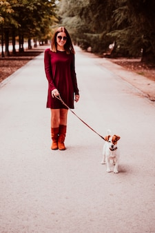 Young woman and her jack russell dog walking in a park