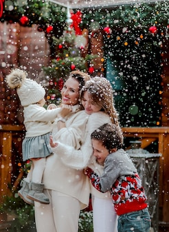 Young woman and her kids in winter sweaters posing in the back yard with christmas background. snowing.
