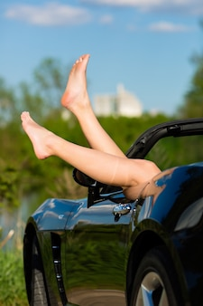 Young woman or her legs in a cabriolet