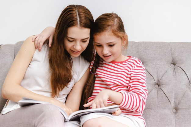 Young woman and her little girl daughter sitting reading books on sofa at home