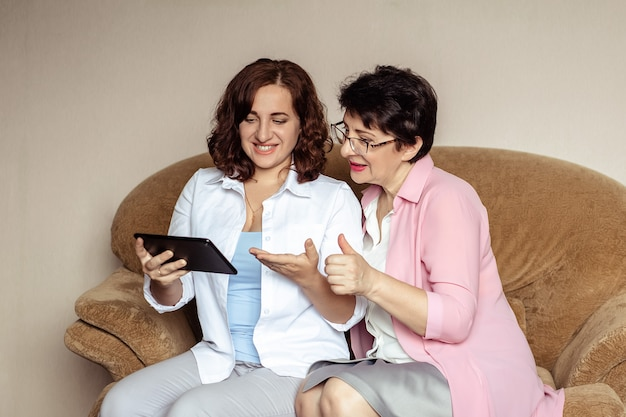 A young woman and her mother, 60 years old, communicate on the tablet using video communication.