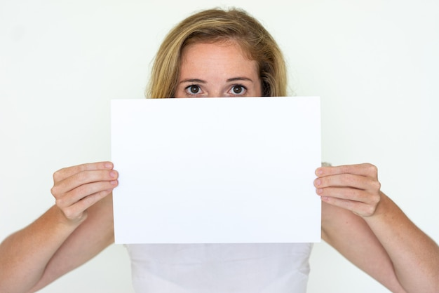 Young woman hiding behind blank sheet of paper