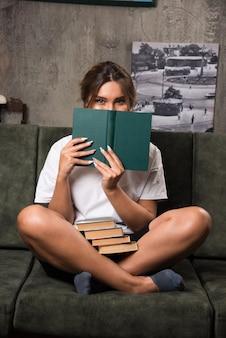 Giovane donna che si nasconde dietro il libro sul divano.