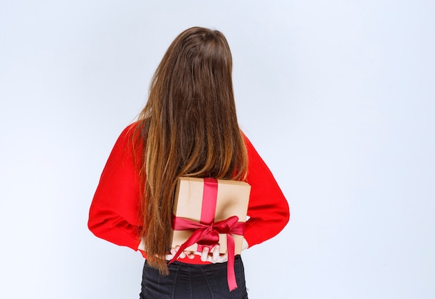 Young woman hiding a cardboard gift box behind herself.