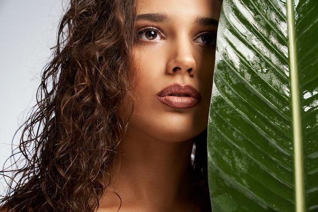 큰 녹색 잎 뒤에 얼굴을 숨기고 젊은 여자 프리미엄 사진