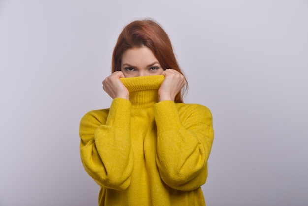 Young woman hiding face in turtleneck