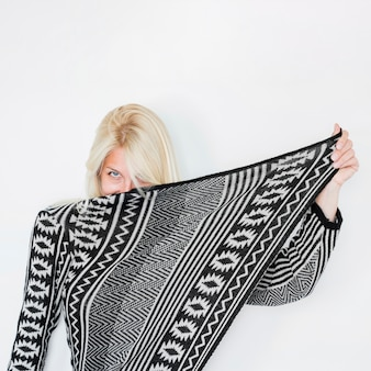 Young woman hiding face behind warm apparel