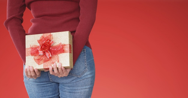 Young woman hiding gift box behind, on red