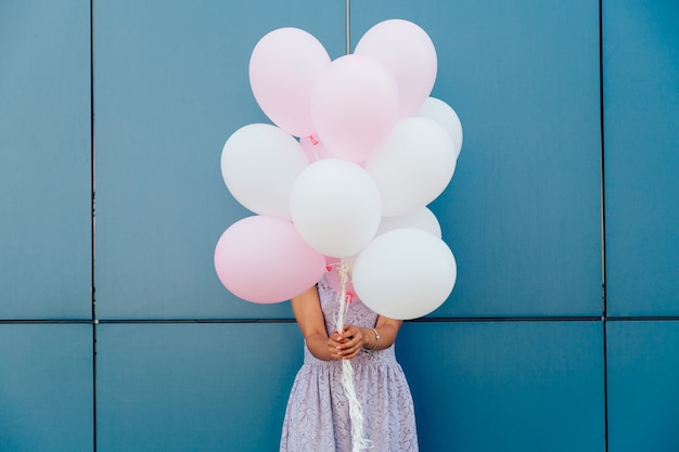 Young woman hiding her face with bunch of balloons, standing against blue wall.