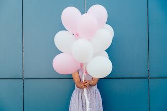 青い壁に立って、風船の束と彼女の顔を隠す若い女性。