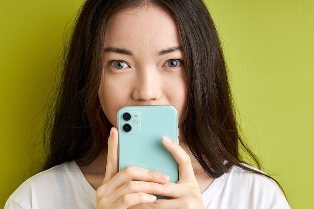 비밀 정보를 숨기는 젊은 여자, 녹색 배경에 고립 된 스마트 폰의 메시지, 휴대 전화에서 비밀 유지