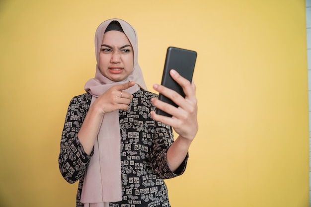 Young woman in hijab disgusted while looking at smartphone screen with hand pointing gesture