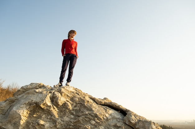 Young woman hiker standing alone on big stone in morning mountains. female tourist on high rock in wild nature. tourism, traveling and healthy lifestyle concept.