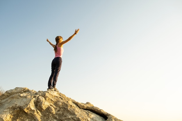 Young woman hiker standing alone on big stone in mountains. female tourist raising her hands up on high rock in morning nature.