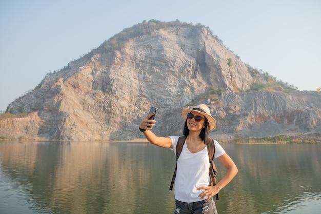 Путешественник молодой женщины использует смартфон, делающий фото на путешествии на вершину горы и активном образе жизни.