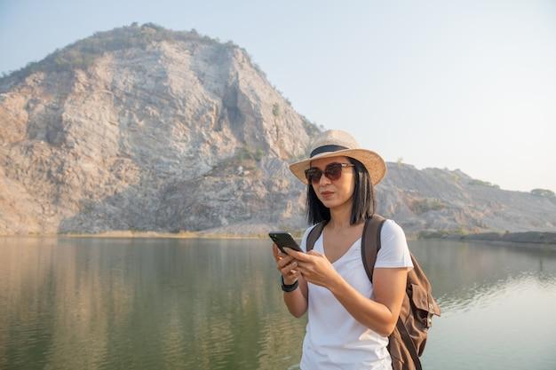 若い女性のハイカーは山で写真を撮るスマートフォンを使用します