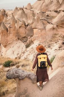 Young woman hiking and enjoying mountain landscape in cappadocia