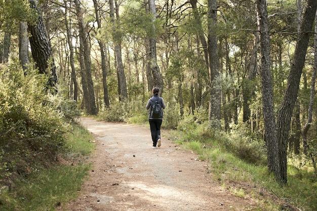 森でハイキングする若い女性