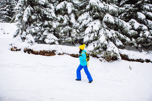 Young woman hiking in snowed winter forest copy space