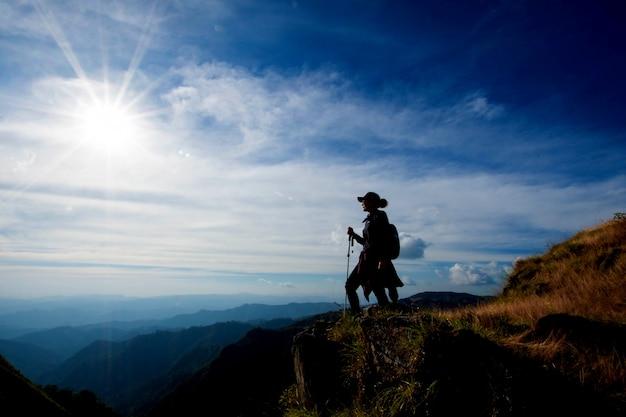 플레어 및 광각 렌즈 화창한 날에 최고의 산에 스탠드를 하이킹하는 젊은 여자.
