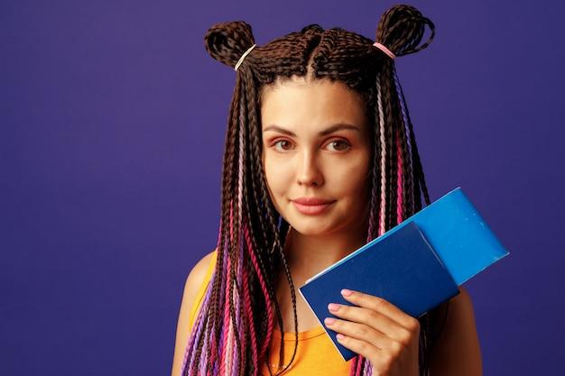 Молодая женщина-хиппи, держащая в руках паспорт и карту