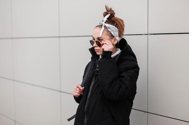 야외에서 흰 벽 근처에 검은 선글라스에 트렌디 한 두건에 세련된 헤어 스타일이있는 가죽 배낭과 세련된 긴 재킷에 젊은 여성 소식통. 미국 소녀. 현대 패션.