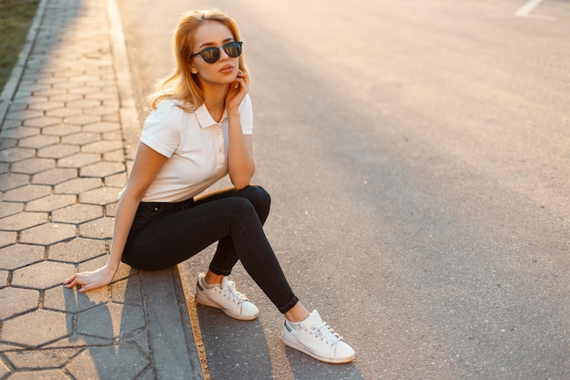흰색 유행 운동화에 검은 청바지에 흰색 폴로 셔츠에 세련된 선글라스에 젊은 여자 소식통은 아스팔트에 앉아