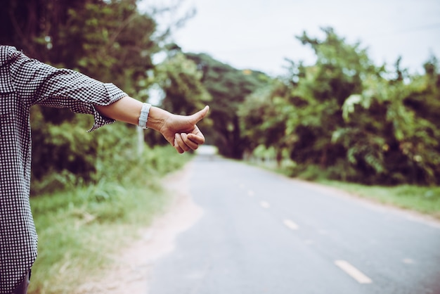 Young woman hitchhiking along a road.