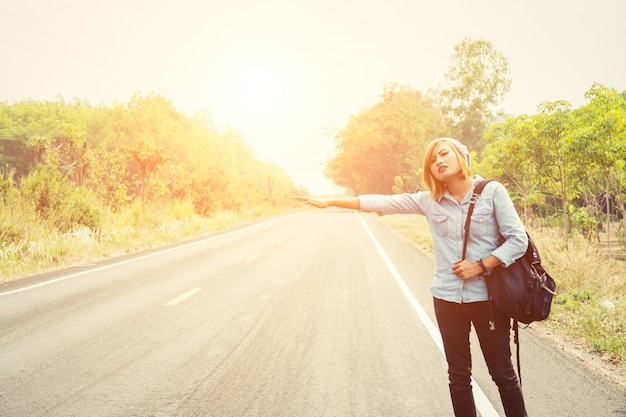 Young woman hitchhiking on a road