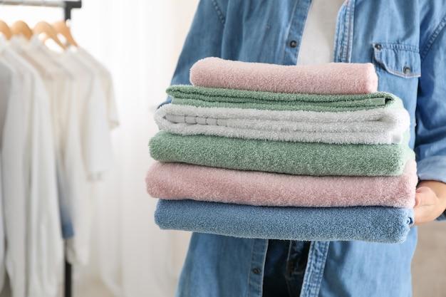 若い女性は清潔なタオルを保持し、クローズアップと