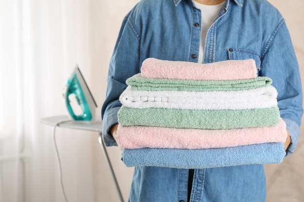 Young woman hold clean towels, close up and