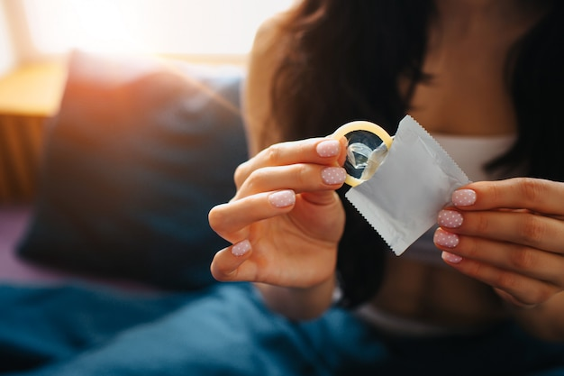 Young woman hold condom in hand. sexual safety