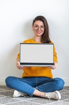 젊은 여성은 흰색 배경에 카펫에 앉아 노트북 빈 모의 화면을 손에 들고