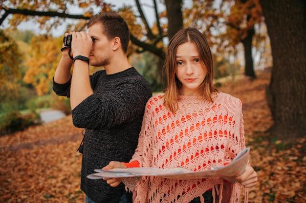 Молодая женщина держит карту и смотрит на camer.a она расстроена. парень посмотри в бинокль. они осматривают.