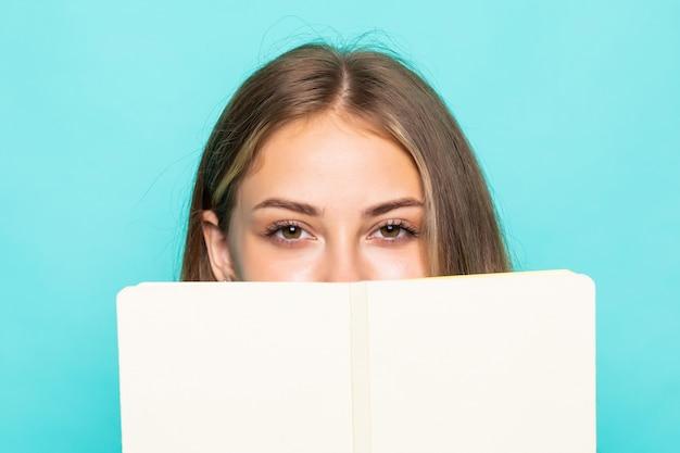 Планировщик удержания молодой женщины пишет личные секреты в журнале изолированной бирюзовой стеной