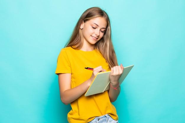 若い女性は、ジャーナル孤立したターコイズブルーの壁にプランナーの書き込みを保持