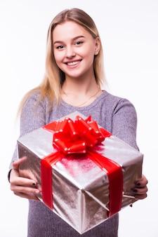 Молодая женщина держит настоящую коробку на белой стене