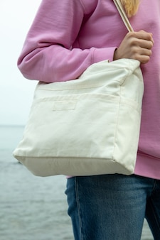 Young woman hold stylish eco bag against sea