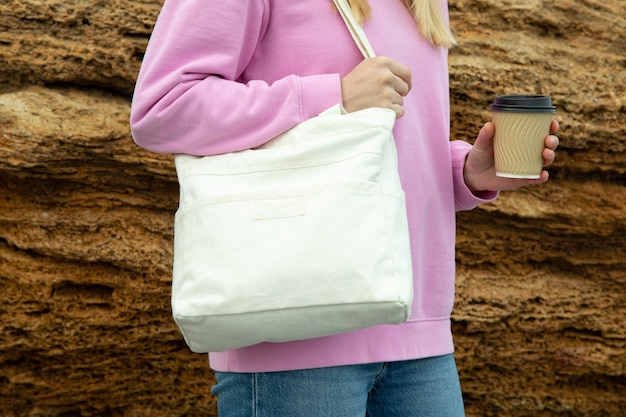 Молодая женщина держит стильную экологическую сумку и бумажный стаканчик на открытом воздухе против большого морского камня