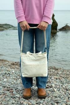Молодая женщина держит стильную эко-сумку на пляже